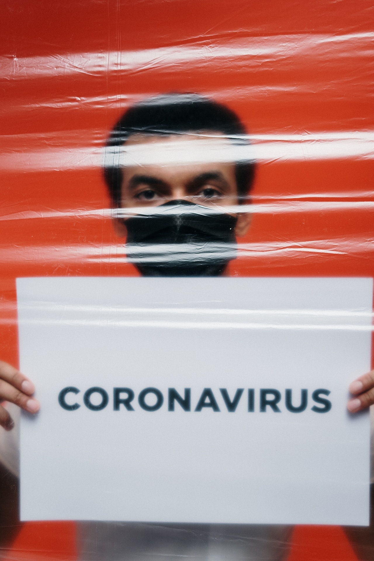 man-with-face-mask-holding-a-poster-with-coronavirus-text-3952183